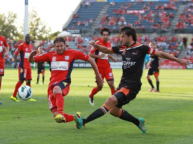Thomas Broich of Brisbane crosses the ball under pressure from Jonathan McKain of Adelaide during the A-League Elimination Final between Adelaide United and Brisbane Roar at Hindmarsh Stadium on April 7, 2013 in Adelaide, Australia.