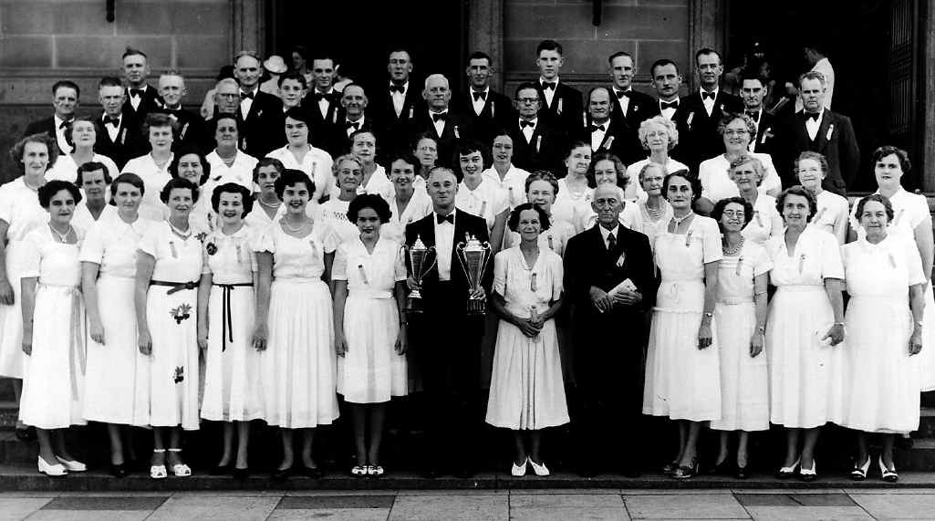 FROM METAL TO MUSIC: Mr Tom Bird (fifth from the right, front) stands proudly with the Silkstone/Booval Choral Union after winning trophies at the Queensland Eisteddfod in Brisbane (c1950s).