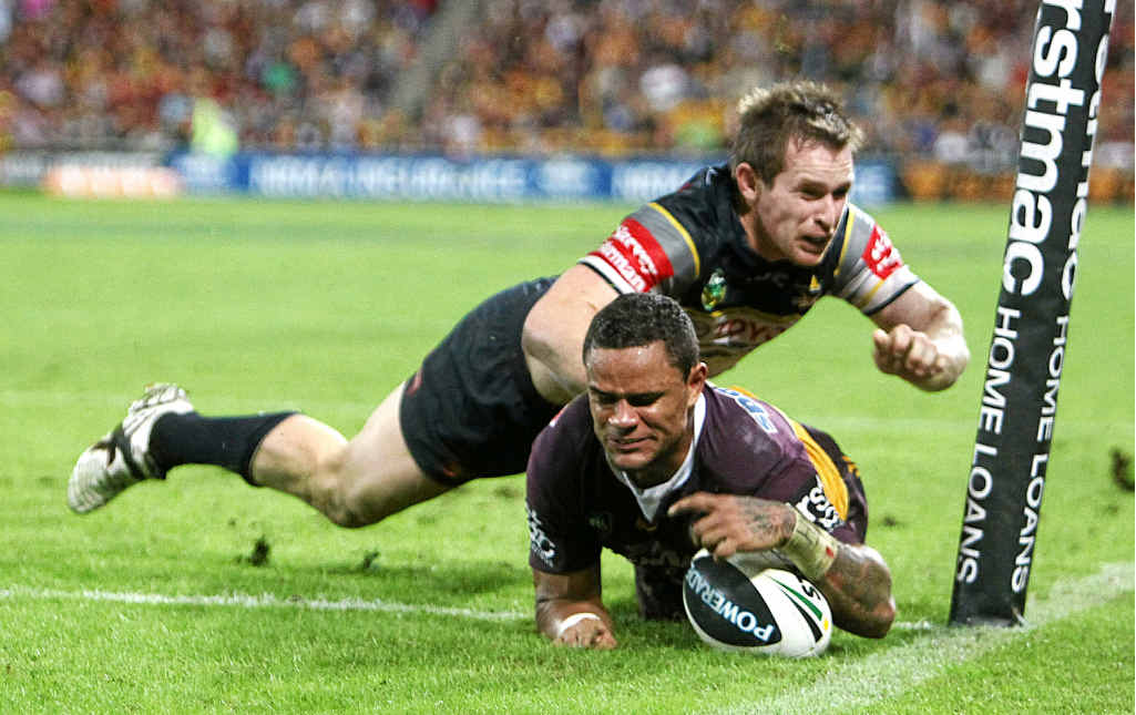 The Broncos' Josh Hoffman scores the winning try in Brisbane on Friday night, evading the tackle attempt of the Cowboys' Michael Morgan.