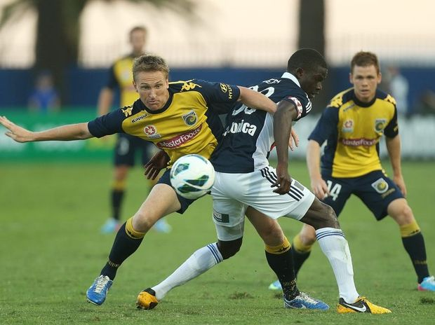 Daniel McBreen of the Mariners competes for the ball with Jason Geria of the Victory during the A-League Semi Final match between the Central Coast Mariners and the Melbourne Victory at Bluetongue Stadium on April 14, 2013 in Gosford, Australia.