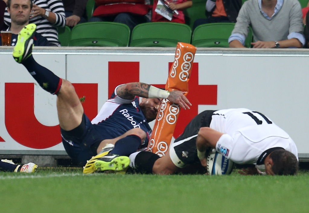 Ronnie Cooke of the Kings scores a try in the corner as Richard Kingi of the Rebels injures his knee during the round nine Super Rugby match between the Rebels and the Kings at AAMI Park on April 13, 2013 in Melbourne, Australia.