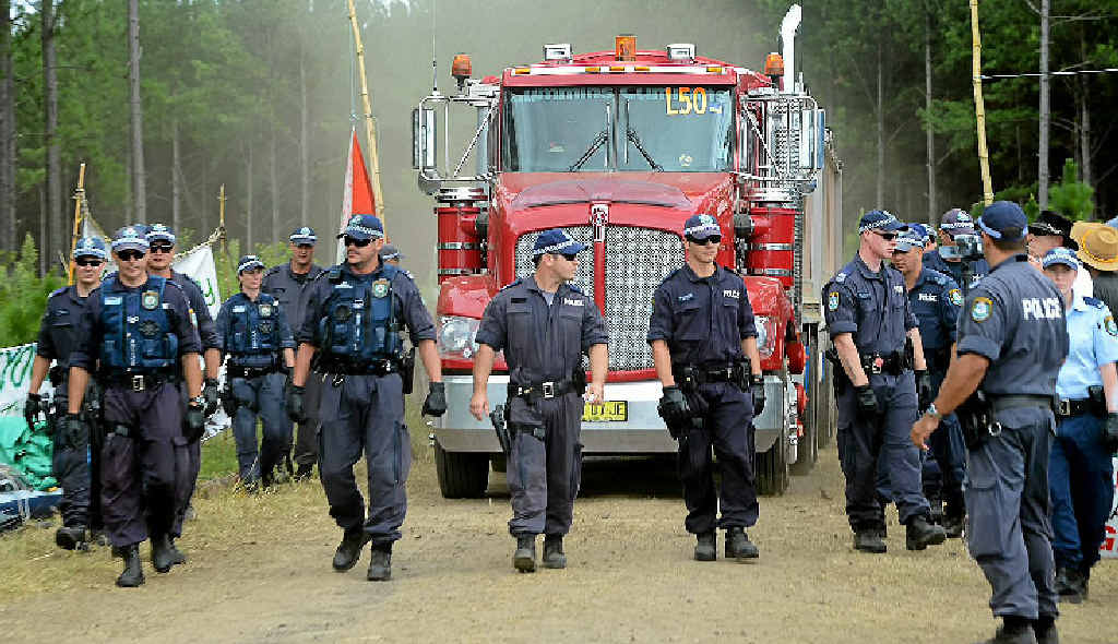SAFE PASSAGE: Police escort a truck from The Doubtful Creek CSG mining site in February.