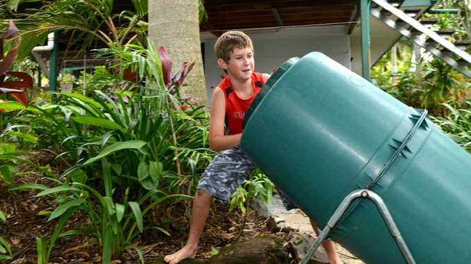 James Sunner gives his mum a hand, spinning the mulcher in their backyard. It's just one of the environmentally friendly features the family has put in place.