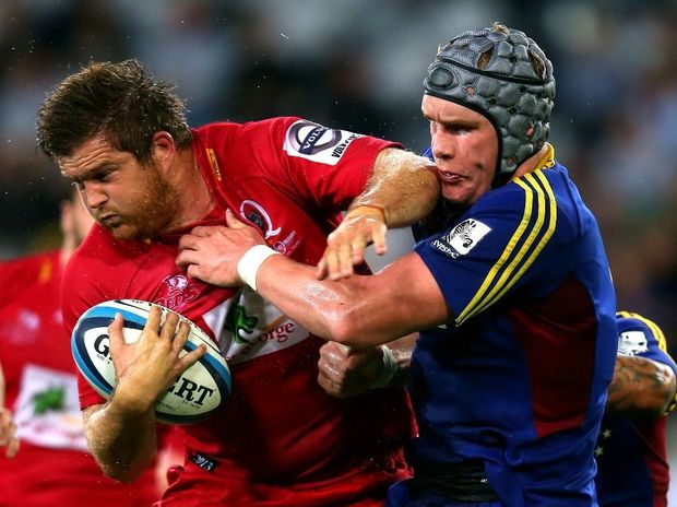 Greg Holmes of the Reds is tackled by Josh Bekhuis of the Highlanders during the round seven Super Rugby match between the Highlanders and the Reds at Forsyth Barr Stadium on March 29, 2013 in Dunedin, New Zealand.