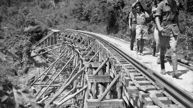 Members of the Military History Section Field Team crossing a trestle bridge near Kinsaiyok, Thailand, Photo Department of Veteran Affairs