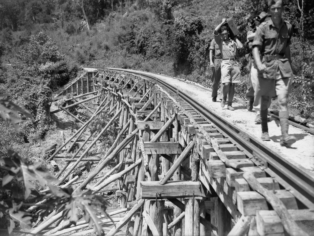 Members of the Military History Section Field Team crossing a trestle bridge near Kinsaiyok, Thailand, Photo Department of Veteran Affairs