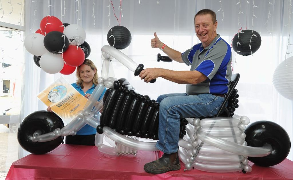 Winner of the shop window competition Stacey Taplin from A Stylish Celebration on Torquay Rd in Pialba with Fraser Coast Ulysses Club sales and marketing manager Warren Jamieson taking the balloon bike for a test ride.