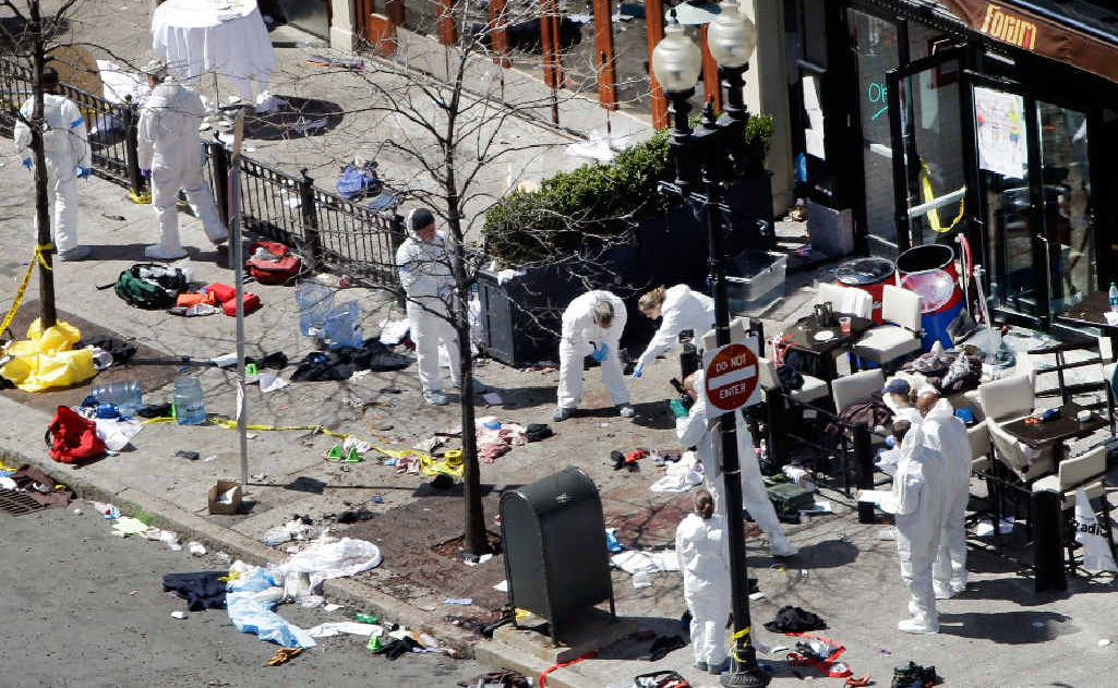 Investigators in haz-mat suits examine the scene of the second bombing near the finish line of the Boston Marathon. The two blasts killed three and injured more than 170 people.