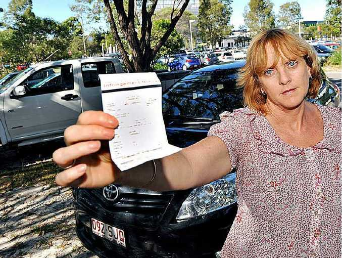 An angry Ann Ross displays a ticket for parking on the grass at the University of the Sunshine Coast.