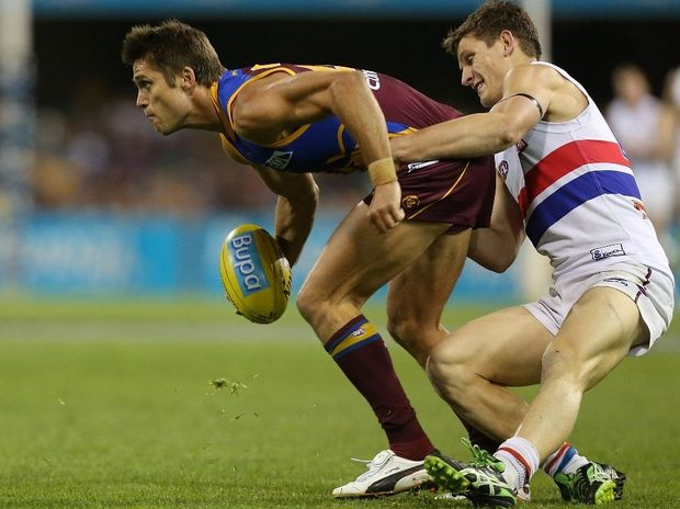 Simon Black of the Lions is tackled by Clay Smith of the Bulldogs during the round 23 AFL match between the Brisbane Lions and the Western Bulldogs at The Gabba on September 2, 2012 in Brisbane, Australia.
