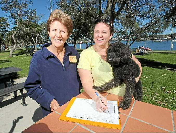 Kelly Richards with dog Jett signs WSPA member Anne Cranitch's petition to end live animal export.