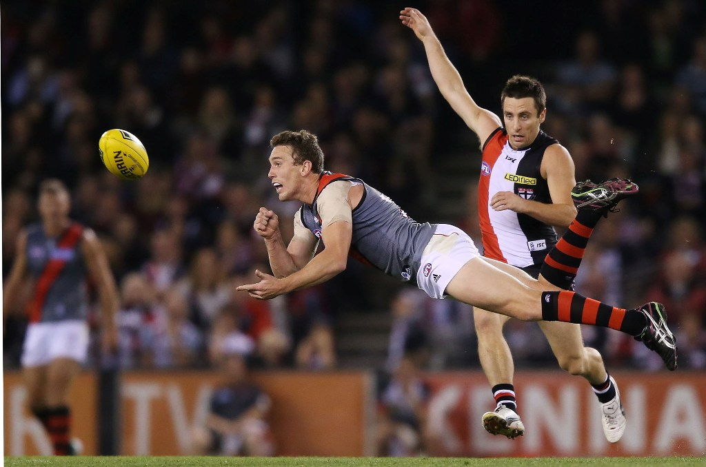 Heath Hocking of the Bombers handpasses the ball away from Stephen Milne of the Saints during the round four AFL match between the St Kilda Saints and the Essendon Bombers at Etihad Stadium on April 20, 2013 in Melbourne, Australia.