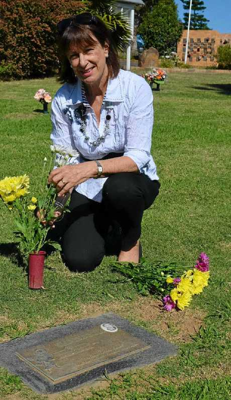 Daughter of Eden Gardens founder Gordon Shaddock, Margaret Hornsey, lays flowers by her father's grave.