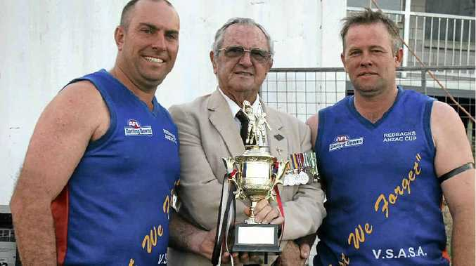 Redbacks coach Jason Wright and captain Clint McErvale receive the Anzac Cup from VSASA member John Palmer.
