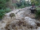 Water and mud flow through a garden after another major water main failure on Nimerette St, Bellbird Park.