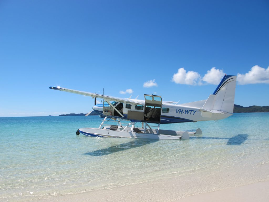 A seaplane lands in turquoise waters at Whitehaven Beach.