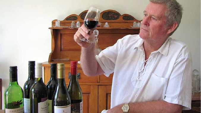 Curra Social and Sports Club member and wine expert Peter Brittain checks out the colour and clarity of a glass of red.