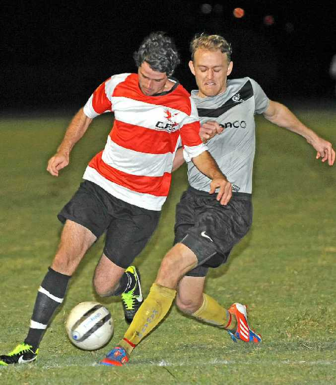 Caloundra's Andrew Carter makes a run into the penalty area, receiving close attention from Kawana's Andrew Frahm.