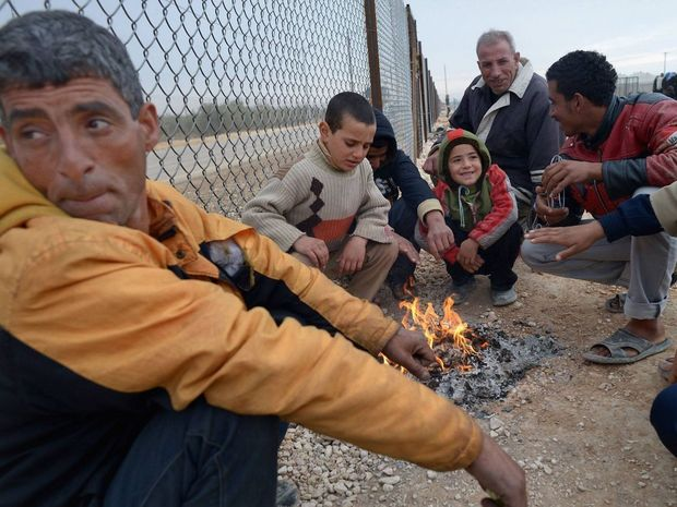 Syrian refugees huddle around a fire to keep warm.