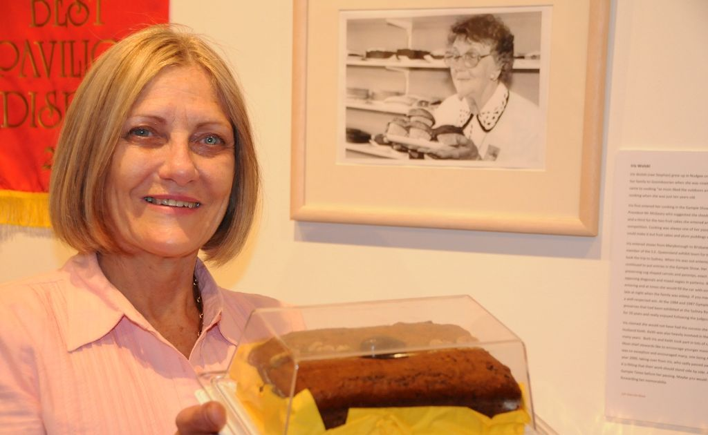 Noela Lewis, daughter of Iris Wolski, known for her cooking and exhibits at many Gympie shows, came from Brisbane to see the exhibition. Noela holds on to a cake baked for the evening's celebration using her mother's recipe.