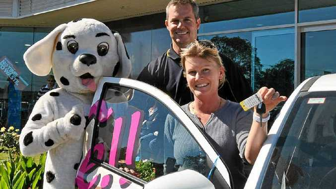Killarney's Donna Barnett was the lucky winner of the Mitsubishi Mirage, pictured with Daily News mascot Daily Dalmatian and Graeme Collins Automotive dealer principal David Cassels.