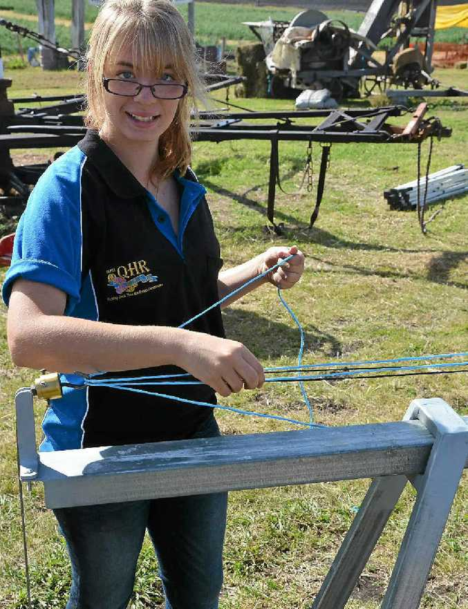 Nichola Yarrow, of Gatton, uses hay string to make dog leads at the Heavy Horse Day.