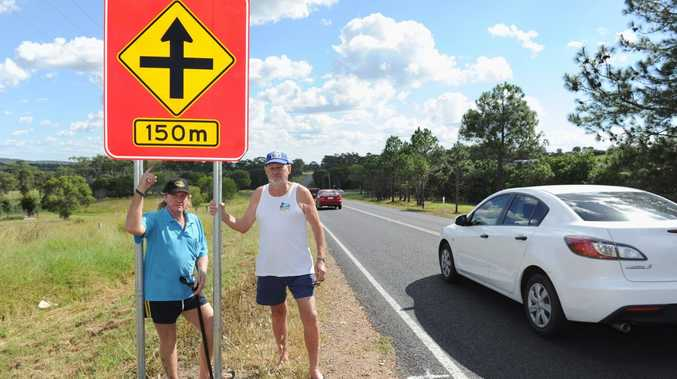 Residents Greg O'Neill and Peter Peterson at a new sign near the Pialba Burrum Heads Rd intersection with Petersens Rd.