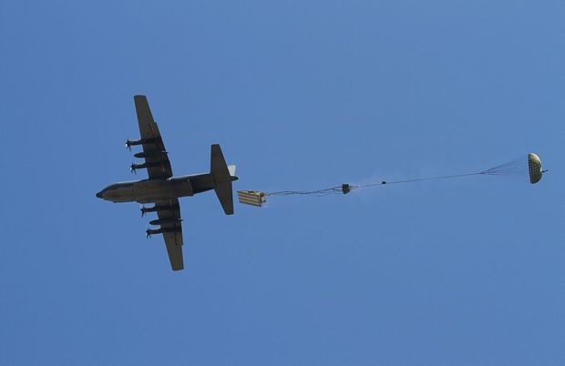 A No. 37 Squadron (37SQN) C-130H Hercules performs an airdrop of a John Deere light tracked bulldozer.