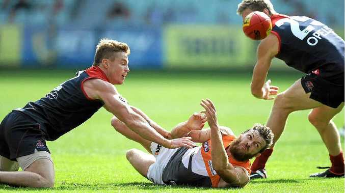 Sam Reid gets the ball away despite the best efforts of Melbourne's Colin Sylvia and Tom McDonald at the MCG last month.