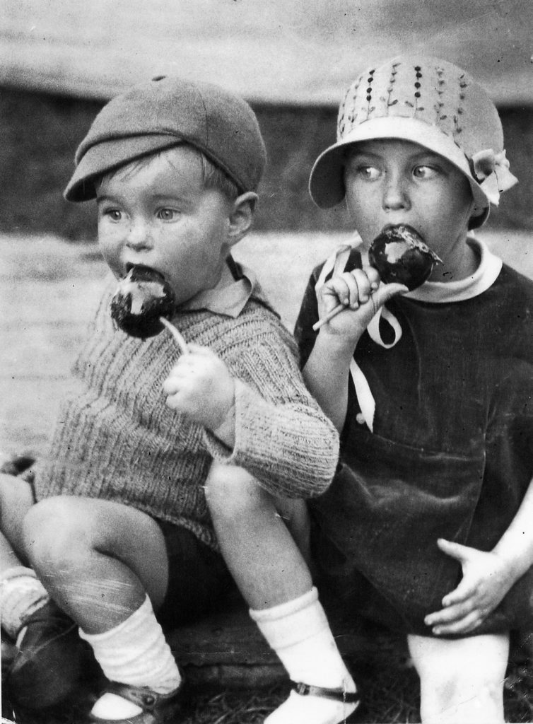 Ken Booth, 2, with sister Wray Duncanson, 4, (nee booth) eating toffee apples at the Ipswich Show in 1934. Photo: File