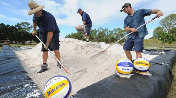 Kevin Hanson, Phil Sanders and Warren Macbeth from the Hervey Bay Boat Club work on the beach volleyball court at Pialba's Seafront Oval.