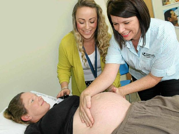 Collaborative Midwifery Clinic facilitator Alison Broderick and student Melanie Williams (in striped USC shirt) assessing pregnant mum Meegan Walker at the USC Collaborative Midwifery Clinic.
