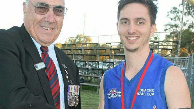 Chaplain Barry Kelly congratulates Anzac medallist Mark Borgert on receiving the most valuable player award.