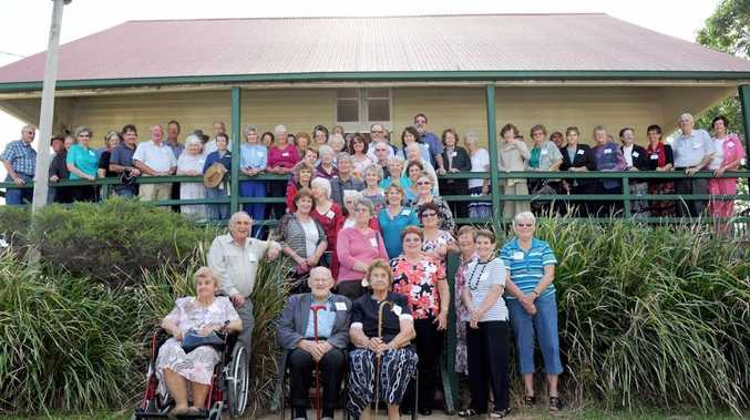 Former students of the school gathered on the front verandah for a group photo at Nikenbah State School's centenary celebrations.