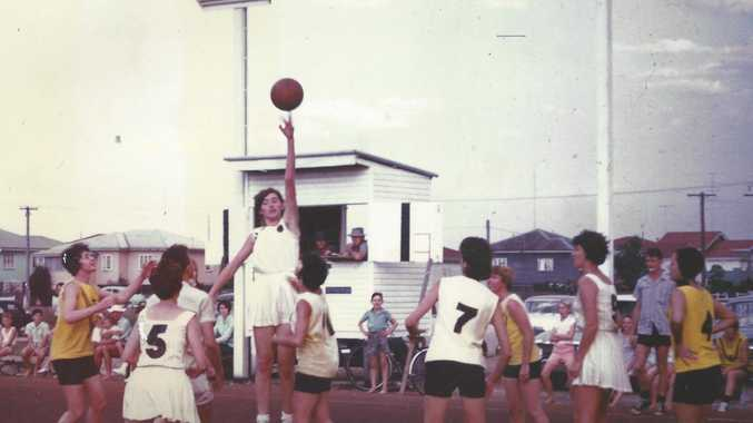 Women's basketball carnival held in 1966 at Ariadne st courts. Two local teams Comets playing against Tigers. Comets player Lyn Christie leaps high for the ball. She is surrounded by No.5 Dawn Byrne (Vollmerhause), No.7 Margaert Curtis (Doolan), No.9 Jill Foster (Lucht), No.4 Toni McCall (Edwards), Moira Pederson (Flemming) and Helene Anderson (Mahoney).