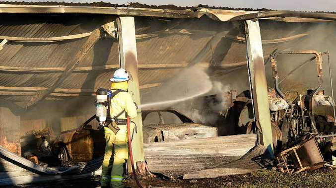 A Gympie Fire and Rescue officer dampens down the scene of yesterday's shed fire on Bath Rd.