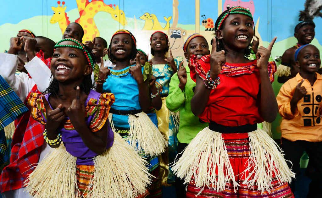 Alimo Prossy (front left) and Namusoke Regina (front right) perform with the Watoto Children's Choir at the Central Church Ipswich.
