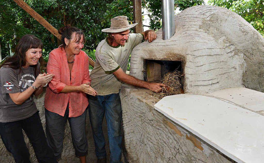 Luke Mathews fires up the new pizza oven at the Mackay Community Gardens as onlookers Danielle Vennik left, and Celeste Philp eagerly wait.