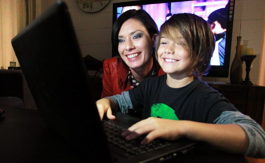 Jarrah Kearney, 8, navigates around the internet on the family laptop with mum, Reef, looking over his shoulder.