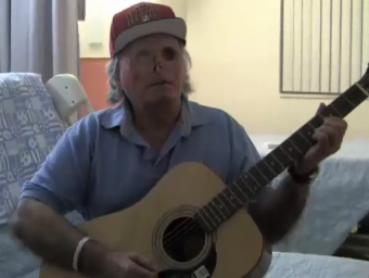 Ronald Poppo playing the guitar.