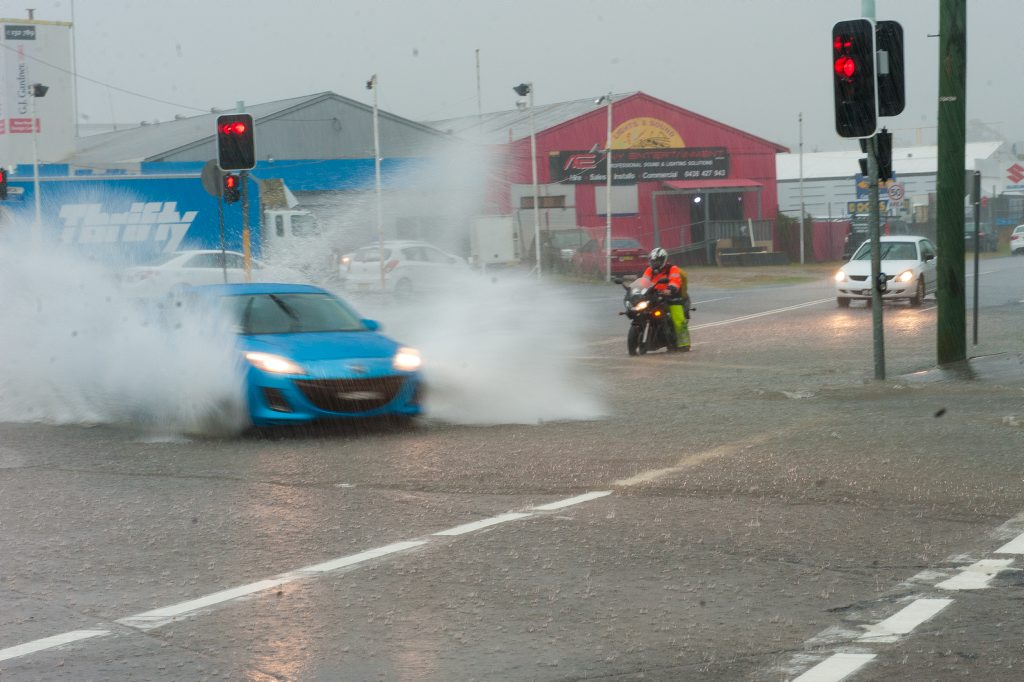 heavy rain hits Coffs harbour. A motor cyclist braces for the back was as a car goes through the Marcia street intersection Photo: Trevor Veale / The Coffs Coast Advocate