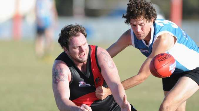 Hervey Bay Bombers' Stuart Buckley gets a hand ball away as Bay Power's Nathan Spencer tries to wrap him up.