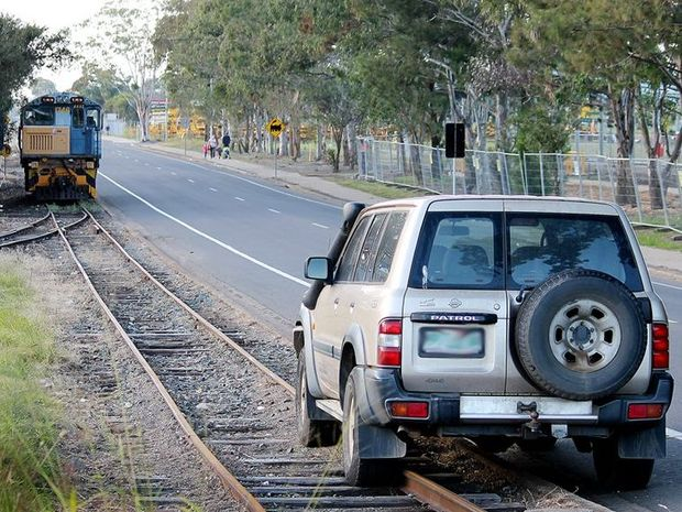 A car parked on the train tracks along lower Kent St is blocking the path of a locomotive on Tuesday morning.