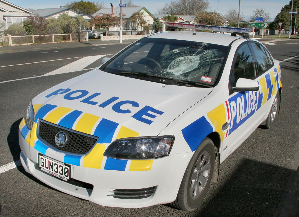 The smashed windscreen of the police car after a man allegedly threw a dive bottle through it.