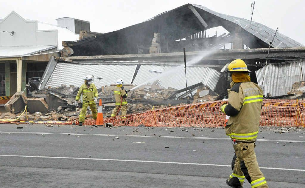 Firemen shoot water on the still-smouldering ruins in Clifton after Sunday morning's fire.