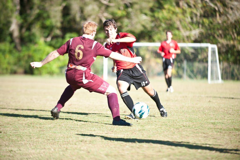 NO WAY THROUGH: Coffs United player Scotty Goddard tries to make a break past Urunga's Grant Holmes. Photo: Rob Wright / The Coffs Coast Advocate