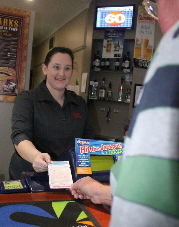 CQ Leagues Club bartender Nadine Henderson receives a winning ticket from the lucky $1.6 million Keno winner in Rockhampton.