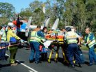 Emergency services wheel a 21-year-old woman involved in a crash at Dundathu to the AGL Action Rescue Helicopter.
