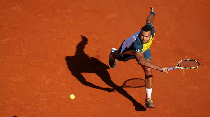 Jo-Wilfried Tsonga of France plays a backhand in his Men's Singles quarter final match against Roger Federer of Switzerland during day ten of the French Open at Roland Garros on June 4, 2013 in Paris, France.