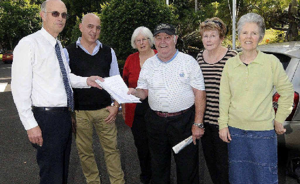 LOVERS OF LITERATURE: Graeme and Janine Wilson, Peter Harris of Lismore Community Action network, Trish Gibson of Friends of the Library and supporter Corena Wynd hand a 904-signature petition to Lismore Council corporate compliance co-ordinator Gianpiero Battista in a bid to save Goonellabah Library.